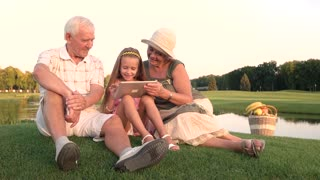 Girl with grandparents holding pc tablet. Granddaughter with grandparents sitting near river with digital tablet. People and modern technology.