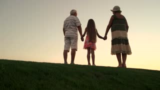 Girl with grandparents on nature background. Slow motion granddaugher holding hands with grandparents and jumping at sunset. Belief and harmony in relationship.