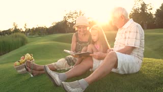 Girl with grandparents outdoors, photo album. People sitting on grass and looking at photos in photo book, basket with fruits. Family on picnic.