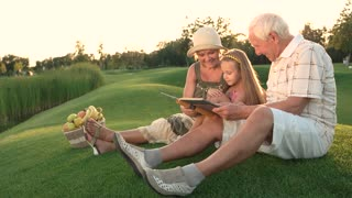 Girl with grandparents, photo album. People looking at photos outdoors. Pages of the past.