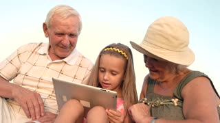 Girl with seniors using pc tablet. Caucasian little girl with gadget outdoors. The possibilities of modern technologies make life easier. Entertainment with gadget on summer nature.