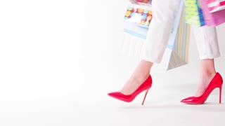 Girl with shopping bags on a white background. Girl in red shoes.