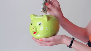 Girl's hand holding money box. Money goes into piggy bank. You can efford luxury vacation. Don't spend everything at once.