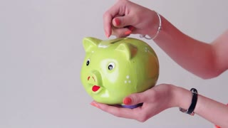 Girl's hand with money box. Coins fall into piggy bank. Save money if you can. Expenses for summer journey.