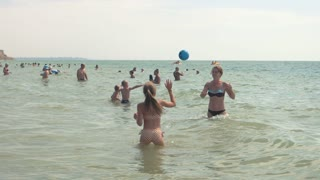 Girls playing in the sea. Crowded beach, daytime.