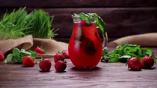 Glass jug of freshness lemonade with strawberries, cranberries and ice.