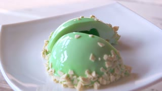 Glazed dessert with delicate flavor. French mousse hemispherical cake covered with mint glaze. Cut in two halves.