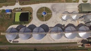 Grain storage tanks, top view. Wheat field.