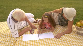 Grandchild drawing with grandparents outdoors. Kid is drawing with colorful pencil. Childs development of art skills.