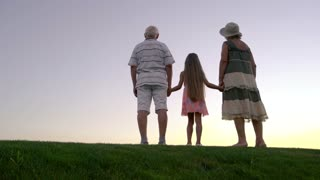 Granddaughter with grandparents, back view. Little girl holding hands with grandparents at the edge of green hill. Enjoying the infinity.