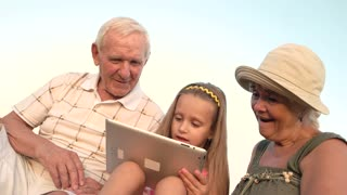 Granddaughter with pc tablet and surprised grandmother. Senior people with grandchild outdoors. Modern technology and skills of kids.