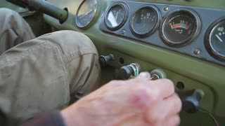 Grandfather starts a retro car. Old military vehicle. Dashboard of an old car.