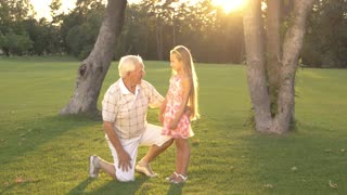 Grandfather talking with granddaughter in park. Grandfather giving wise advice to his grandchild outdoors. Family, generation and people concept.