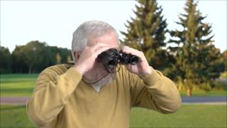Grandfather with binoculars on nature background. Senior man looking through binoculars outdoors. Exploring of summer landscape.