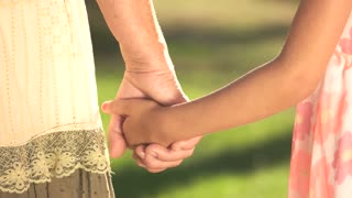 Grandmother and granddaughter holding hands. Senior woman and child outdoors. Warm family relationship.