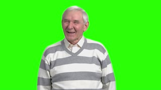 Grandpa laughing at nonesense, slow-motion. Old man laughing because of hogwash against green background.