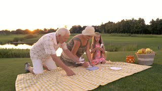 Grandparents and granddaughter outdoors. Elderly people and child setting dishes on a cloth, summer nature background. People on picnic.