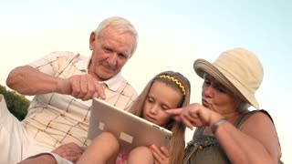 Grandparents and granddaughter playing on pc tablet. Old man and woman with grandchild using digital tablet outdoors. Different generations and modern technology.