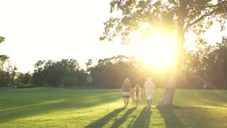 Grandparents and little girl walking in park. Grandchild with grandparents spending time on summer nature background. Happy summer vacation with grandparents.