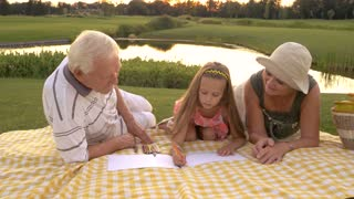 Grandparents helping granddaughter to draw. Little girl and grandparents outdoors. Art skills development.