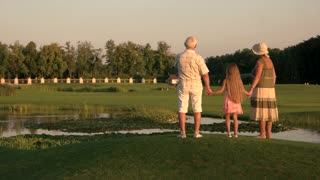 Grandparents with granddaughter walking near water. Seniors with grandchild on green lawn, back view. People and green landscape.