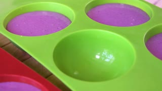 Green silicone molds with purple mousse. Process of cooking french dessert at confectionery. Smooth consistency of mousse.