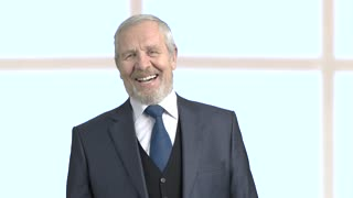 Grey haired businessman laughing on blurred background. Elderly bearded male executive is laughing, slow motion.