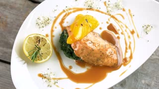 Grilled salmon, vegetables and sauce. Delicious restaurant food top view.