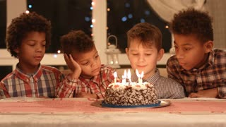 Group of kids blowing cake's candles out. Boys sit near birthday cake. Our guest is here. Visiting school friend's birthday party.