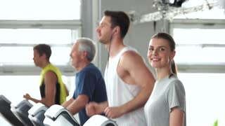 Group of people exercising at gym. Young beautiful woman runs on treadmill and looking at camera. Sport for beauty.