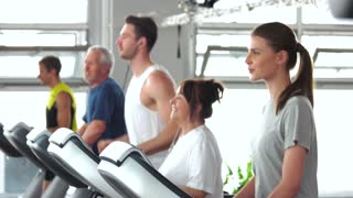 Group of people training on treadmill. Young woman exercising at gym. Sport for all ages.