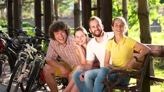 Group of smiling friends on bench in park. Four joyful young cyclists resting outdoors. Group of cheerful friends on summer vacation.