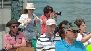 Group of tourists. Woman on boat taking photos.