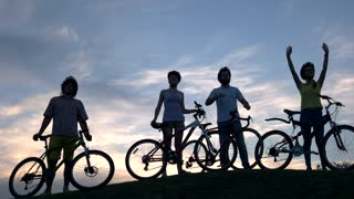 Group of young cheerful cyclists at sunset. Four young friends with bicycles waving with hands on sky background. Unforgettable summer trip.