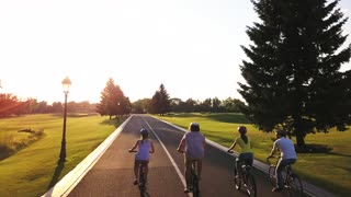 Group of young persons riding bicycles outdoors. Four friends in casual wear cycling on country road, sunny day. Unforgettable summer trip on bikes.