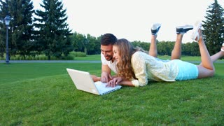 Guy and girl fun talking on the nature. Lovers on holiday. Lovers play on the computer in the park. Honeymoon trip. Happy couple.