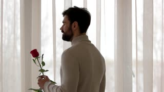 Guy holding flower and phone. Angry man indoor. Disappointed in love.