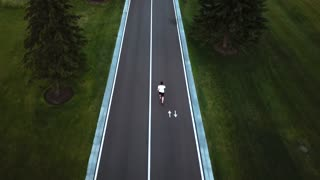Guy running along road, back view. Young athletic man on morning run, aerial drone view. Sport and healthy lifestyle concept.