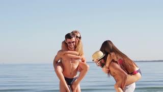 Guys carry girls on backs. Young people near sea smiling. Weekend at Hawaiian coast. Warm sun and good mood.