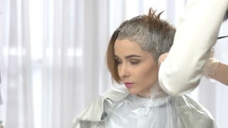 Hair dyeing process. Young woman in beauty salon. Hair dying tips.