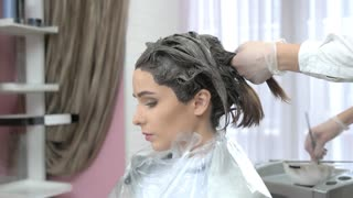Hair dying, side view. Caucasian woman in beauty salon.
