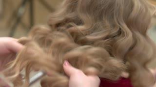 Hair of a little girl. Female hands, blonde wavy hair.
