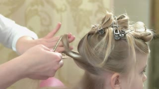 Hairdo of child closeup. Hands of hairdresser and barrettes.