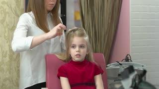 Hairdresser and little girl. Child in hair salon.