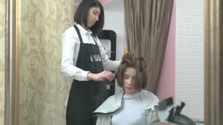 Hairdresser using a blow dryer. Hair salon employee and customer.