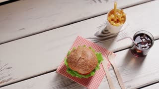 Hamburger with cutlery and drink. Junk food menu on table. Burger menu on wooden background. Small snack in city diner.