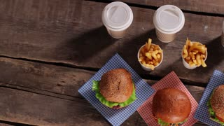 Hamburgers with fries on table. Top view of fast food. New dishes from the menu. Buy more and get discounts.