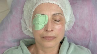 Hand applying alginate face mask. Mature woman, cosmetology procedure. Best natural skin care products.