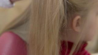 Hand brushing hair close up. Straight blonde hair.