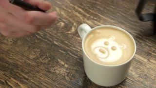 Hand making latte art bear. White mug with coffee, wood. Cafe barista jobs.